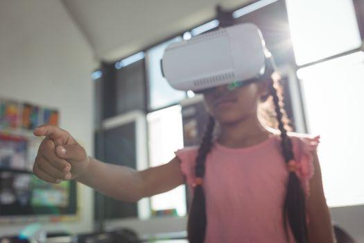 Girl wearing virtual reality simulator in classroom