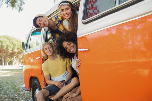 Portrait friends looking through camper van