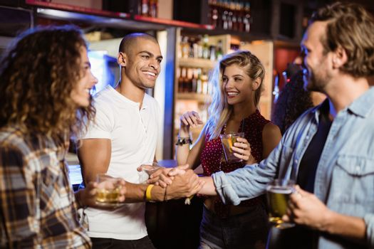 Male friends doing handshake at counter in counter in club