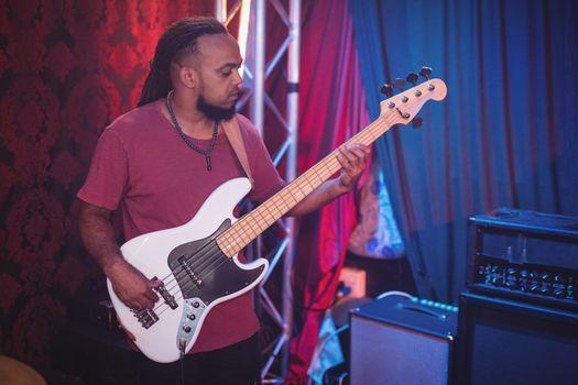 Musician playing guitar at nightclub