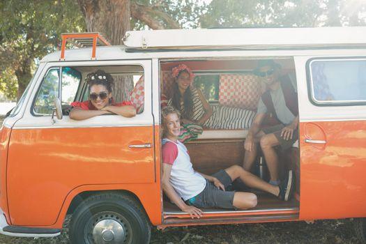 Portrait of friends sitting in camper van