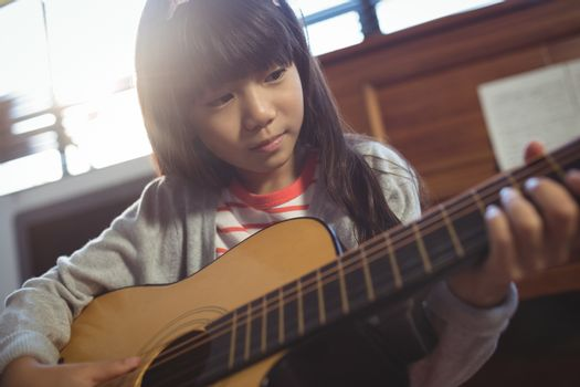 Concentrated girl practicing guitar
