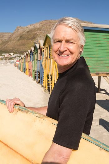 Man carrying surfboard while standing against beach huts