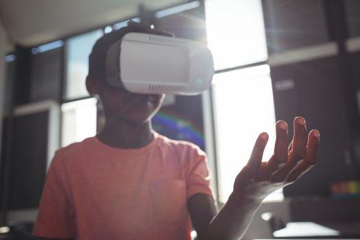Boy wearing virtual reality simulator against windows