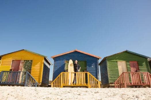 Man standing with surfboard at beach hut