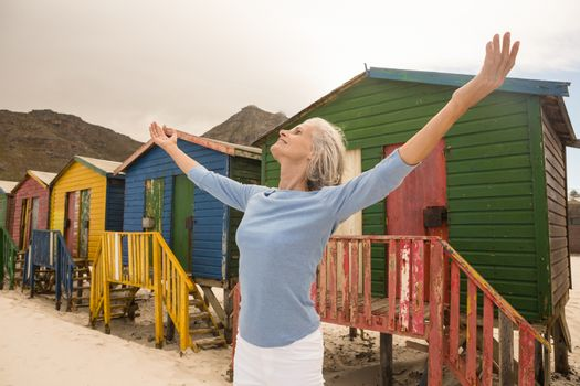 Woman with arms outstretched standing against huts