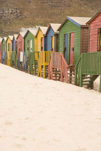 Multi colored wooden huts on sand against mountain