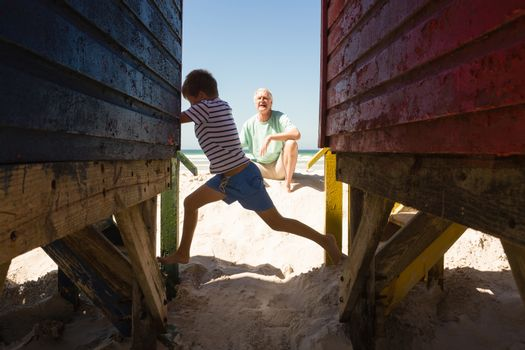 Happy boy playing with grandfather by huts