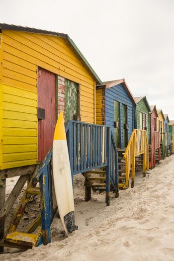 Surfboard by wooden hut at beach