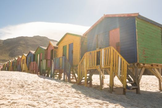 Colorful huts on sand against mountain