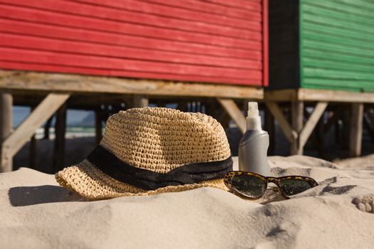 Close up of sunhat and sunglasses on sand against hut