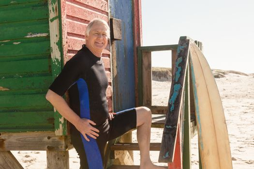 Portrait of man standing by hut at beach