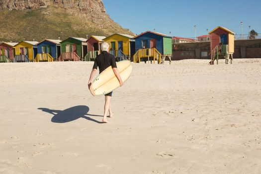 Man with surfboard walking on sand against beach huts