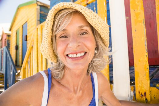 Portrait of smiling woman against beach huts