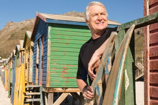 Man looking away while standing against beach huts