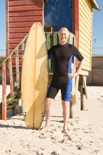 Portrait of man with surfboard standing against hut