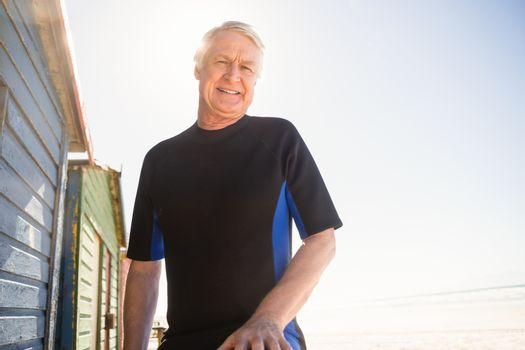 Portrait of smiling senior man standing by beach huts