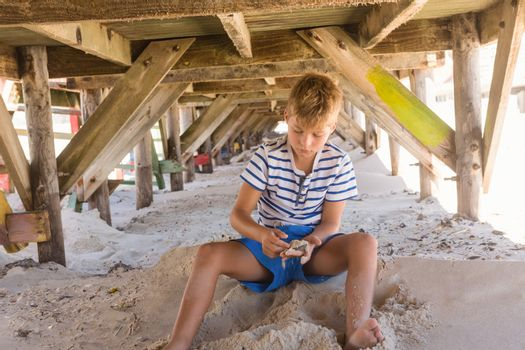 Boy  playing with sand under hut