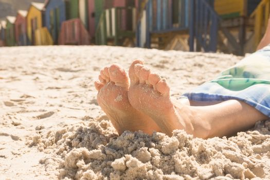Low section of woman sitting on sand against beach huts