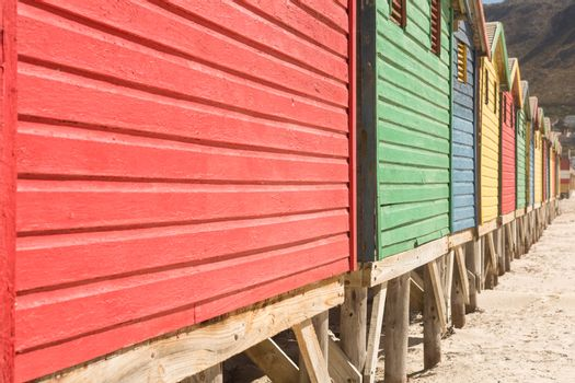 Crooped image of wooden huts on sand