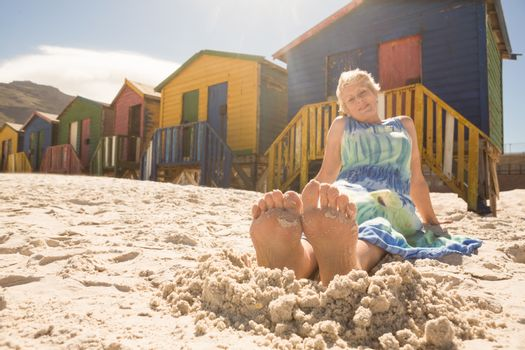 Woman relaxing on sand against huts at beach