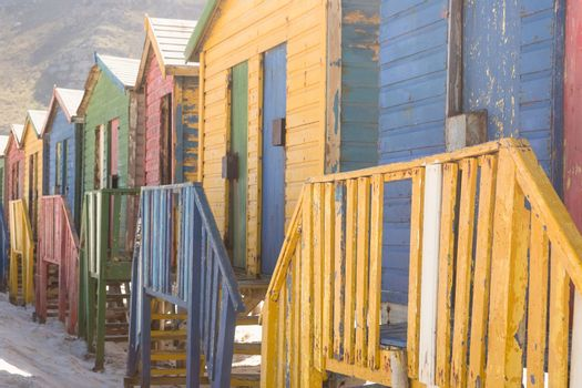Close up of multi colored wooden huts on sand
