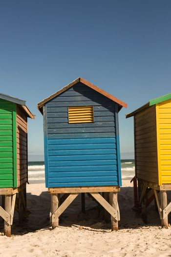 Colorful huts on sand against clear sky