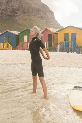 Senior woman stretching while standing by surfboard against huts