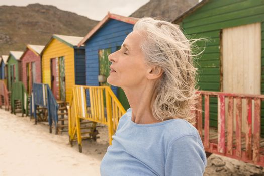 Close up of woman with eyes closed standing against huts