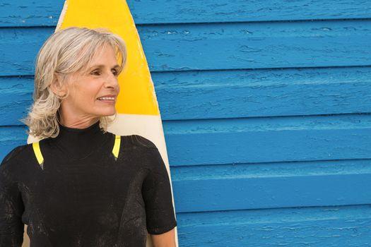 Senior woman standing against blue hut