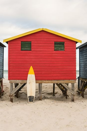 Surfboard by red wooden hut at beach