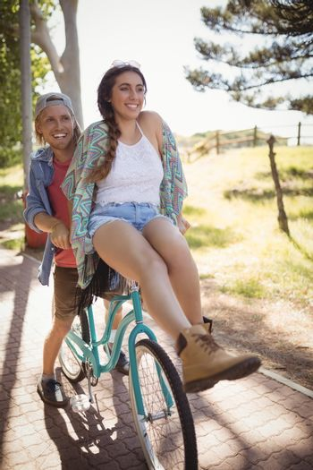 Smiling couple sitting on bicycle at footpath