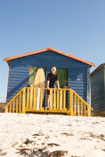 Portrait of man standing with surfboard in hut