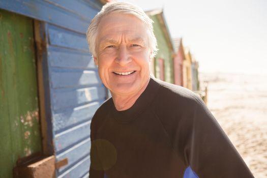 Portrait of senior man standing by beach huts
