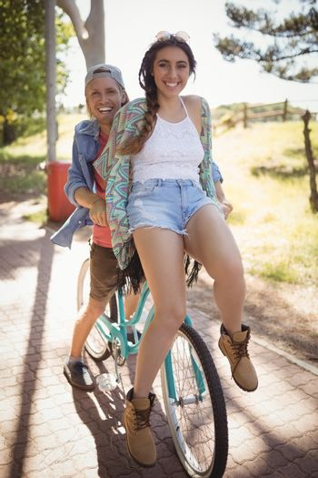 Playful couple sitting on bicycle at footpath