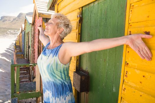 Senior woman with arms outstretched standing by huts