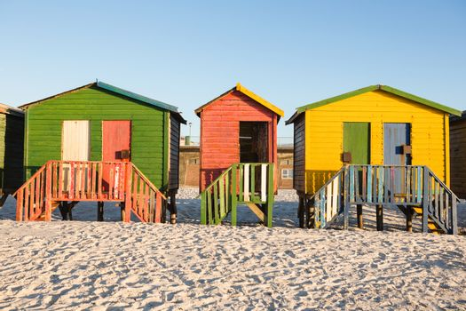 Multi colored huts on sand against clear sky