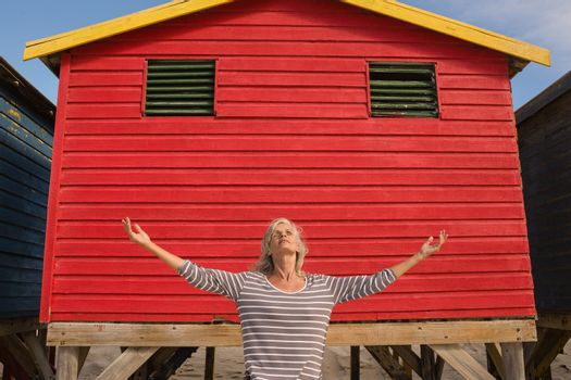 Woman standing against red hut