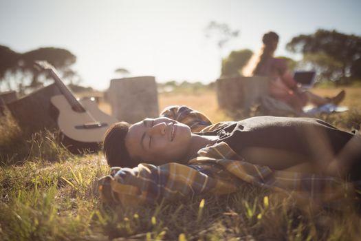 Ypung man resting on grassy field