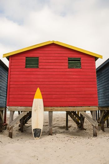 Surfboard by red hut on sand at beach