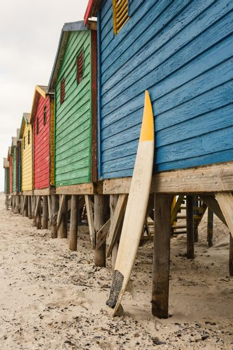 Surfboard by blue wooden hut at beach