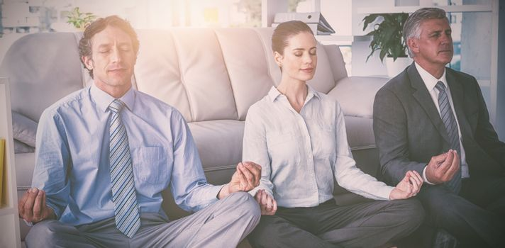 Business people practicing yoga in office