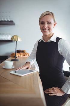 Smiling waitress at counter