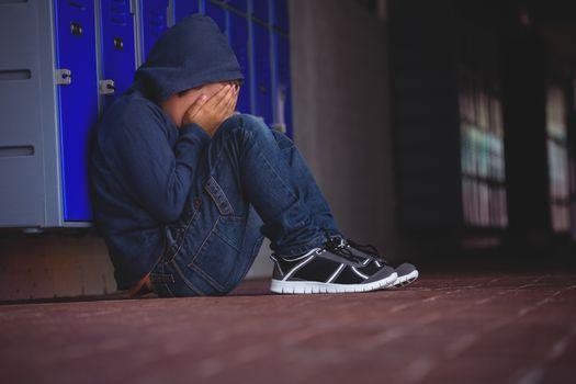 Boy sitting on pavement by lockers
