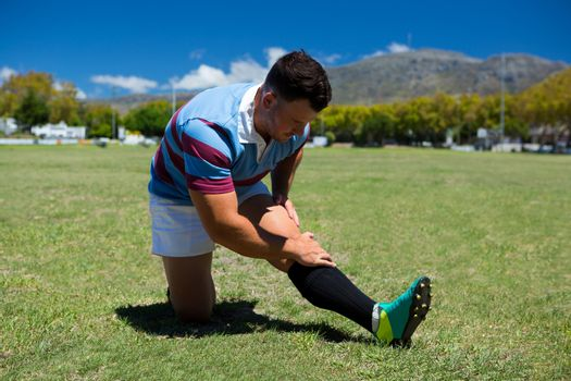 Young rugby player stretching on grassy field