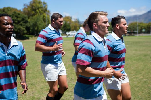 Close up of rugby team jogging at grassy field
