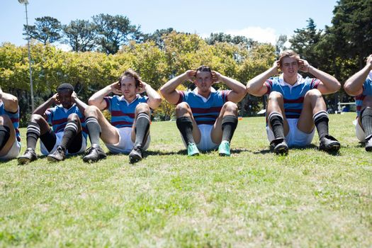 Portrait of rugby players exercising at grassy field