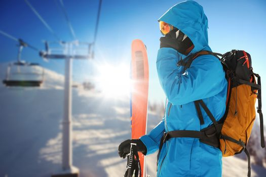 Composite image of skier talking on phone while holding skis