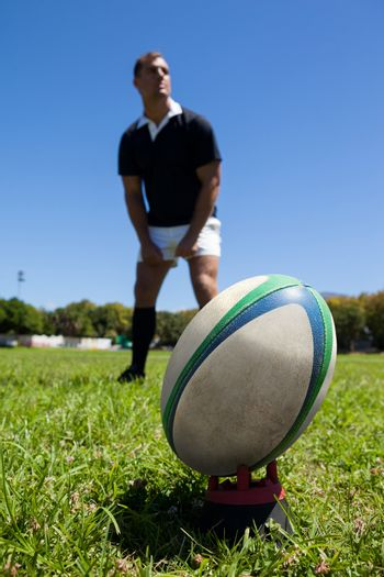 rugby ball against player on grassy field