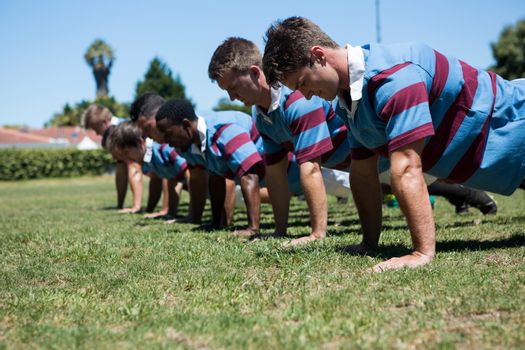 Close up of players doing push up at grassy field